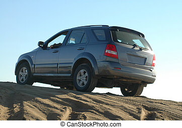 Fun on the beach - A four-wheel-drive in the top of a sand...