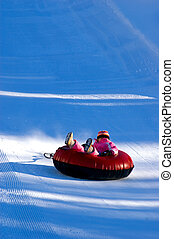 tubing - child in pink snow suite on red inner tube speeding...