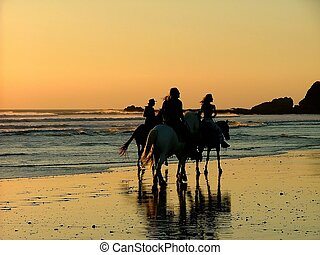 tres hombres - three people on horseback riding on wet sand...