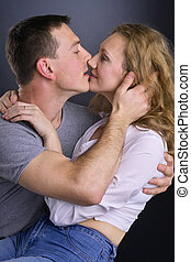 Kiss - family portrait of a young and happy couple kissing
