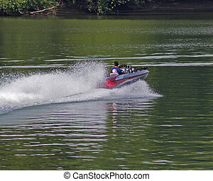 Boat spray - Speed boat running on river with spray flying...