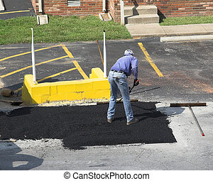Its hot - City crews working on street repair patching holes...