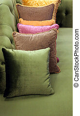 Pillows - Row of beautiful cushions lined up on a green sofa