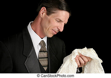 Remembering You - A grieving widower holding his wifes dress...