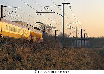 High speed train passing by at sunset in north of France