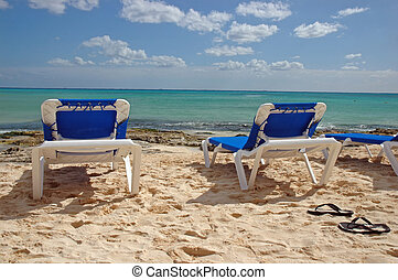 Blue Beach Chairs - Blue beach chairs sit empty on a sandy...