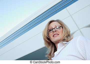 Corporate woman standing beside office building