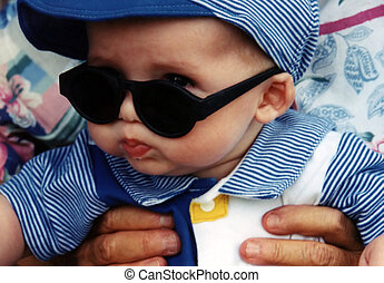 Cool Dude - Infant with sunglasses, held by grandmother.