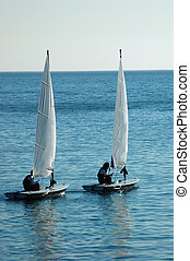 sailing - a couple of sail dinghies out in the ocean