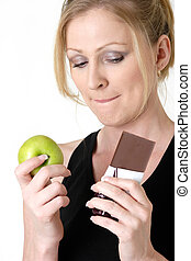 Making a choice - woman holding an apple and chocolate bar...