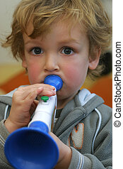 Blowing Hard - A young boy blowing hard into a toy trumpet