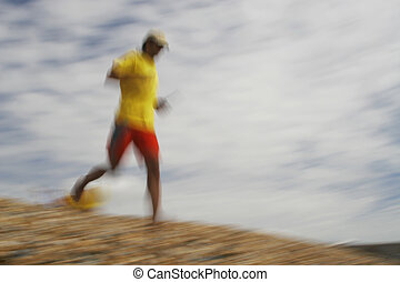 Rescue - A motion blurred shot of a lifeguard running down...