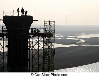 Bridge Builders - -- workers on a pier in a river in...