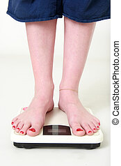 Weight watching - womans feet standing on a scale on white