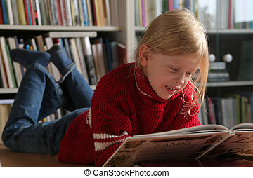 Reading a book - A little, blond girl lying and reading a...