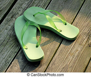 Flip Flops - Green flip-flops against brown wood of a beach...