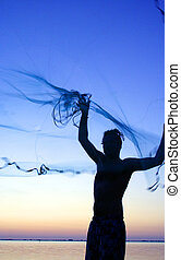 young man and net 4 - young man throwing castnet at sunset...