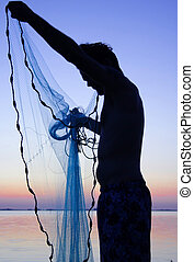 young man with net2 - young man throwing castnet at sunset...