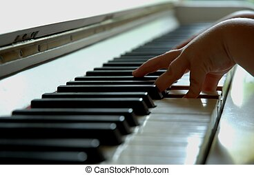 child playing piano - the hand of a 4 year old playing the...
