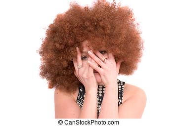 Hiding - Pretty girl with red afro wig hiding her face in...