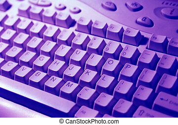 Technology - Angled shot of computer keyboard, tinted blue.