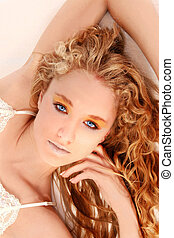 Emma - Young woman with long blonde curly hair and blue eyes...