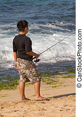 Boy Fishing on the Beach - Photo of a boy fisihing on the...