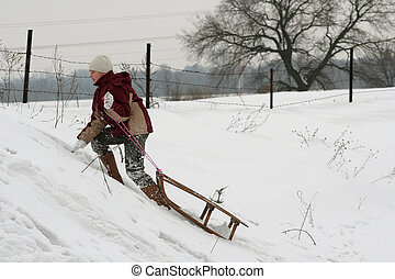 Winter fun - A young girl pulling her sled