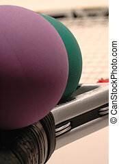 racquetballs and racquet - macro focus on gray racquet and...