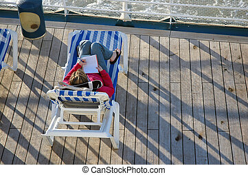 Cruise Writer - A young woman writes on the rear deck of a...