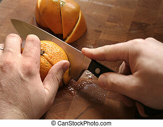 orange cut - hands slicing oranges on wooden cutting board
