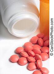 spilled pile of red tablets beside two medicine bottles