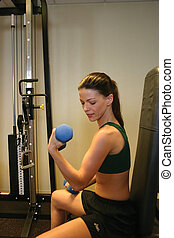 Woman doing Curls - Pretty woman lifting weights in a gym