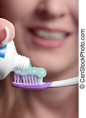 Toothpaste on toothbrush up close with woman face in the...