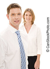Business People - A businessman stands in front of a female...