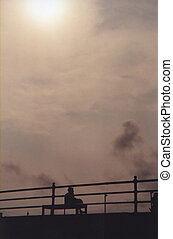 Isolation - A silhouetted woman sitting alone on a bench on...