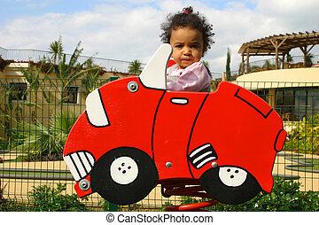 Learning to Drive - A young mixed race girl sitting in a red...