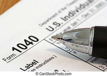 Income Tax - Close view of a pen and a US tax form 1040