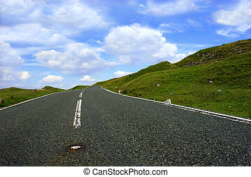 The Road Ahead - Steep uphill road with grass verges on...