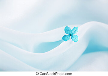 Blue Flower - Light cloud-blue fabric background with flower