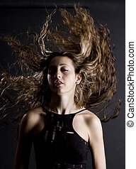 Amazing Hair - A woman flicks her amazing hair above her...