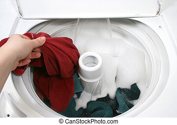 washing clothes - putting clothes into washer