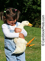 Struggling with the Duck - Young girl struggling and...