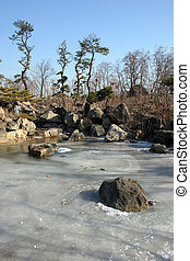 Frozen pond - Pond frozen over with waterfall in the...