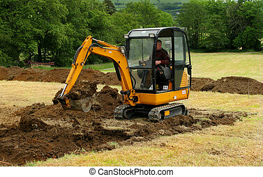 Mini Digger In Action - Man operating a mini digger in a...