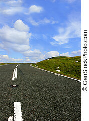 Up the Hill - A low perspective of a rural road with a grass...