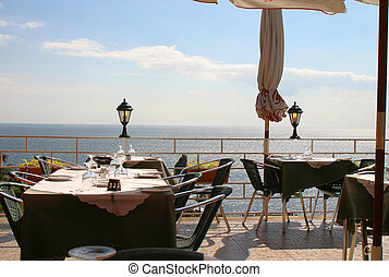 Empty Tables - A restaurant looks out across the sea in...