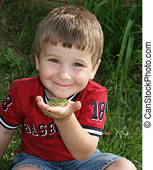 Silly frog - A small boy holding a green tree frog