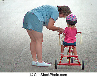 Tricycle Training - Woman showing child how to ride a...