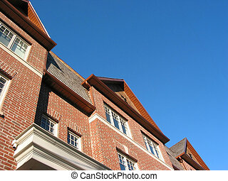 New brick townhomes on the background of bright blue sky